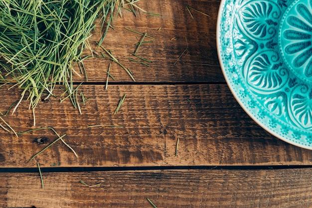 Moderno e fresco. vista dall'alto della piastra del modello sdraiata su un tavolo rustico in legno con erba