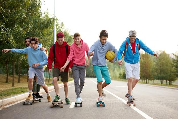 Ragazzi moderni e amichevoli in abiti casual che fanno skateboard e mostrano trucchi emozionanti