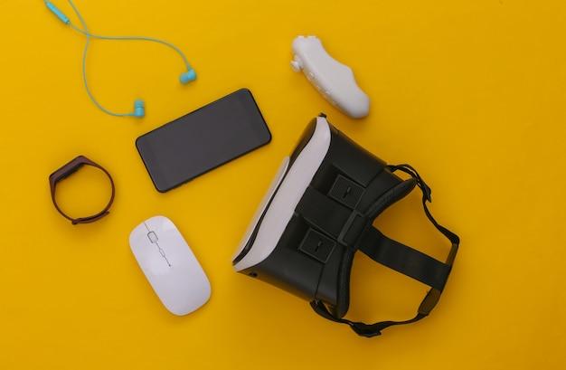 Gadget e dispositivi moderni. cuffie per realtà virtuale con smartphone, controller, auricolari, braccialetto intelligente, mouse per pc su sfondo giallo. vista dall'alto. scuotila