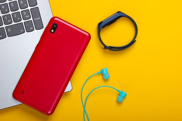 Gadget moderni. laptop, smartphone e braccialetto intelligente, auricolari sottovuoto su giallo