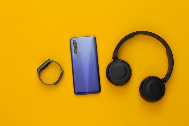Gadget moderni. smartphone moderno con cuffie stereo nere e un braccialetto intelligente su un giallo