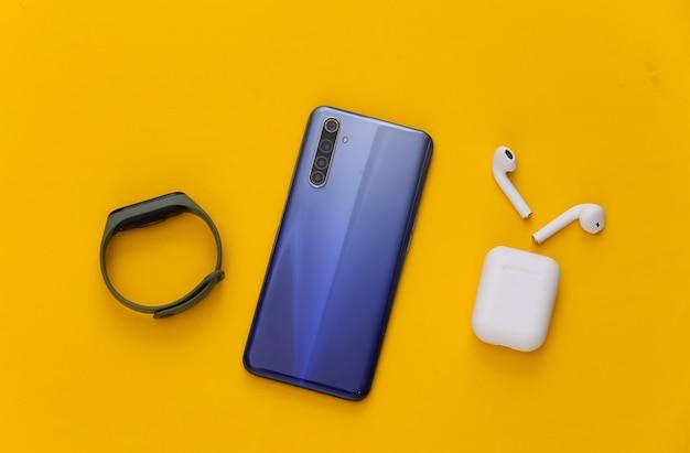 Gadget moderni. smartphone moderno con auricolari wireless e braccialetto intelligente su giallo. lay piatto