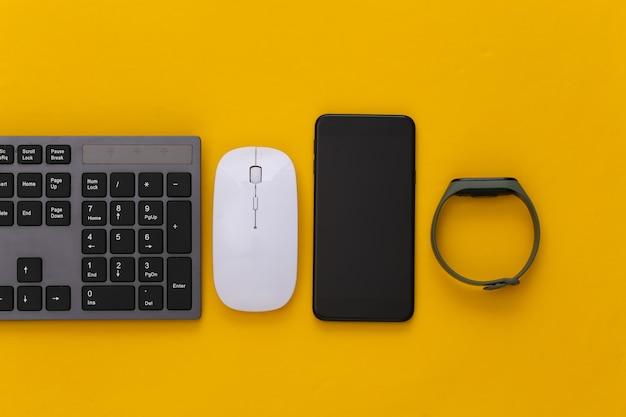 Gadget moderni. tastiera per pc con mouse per pc, braccialetto intelligente e smartphone su giallo