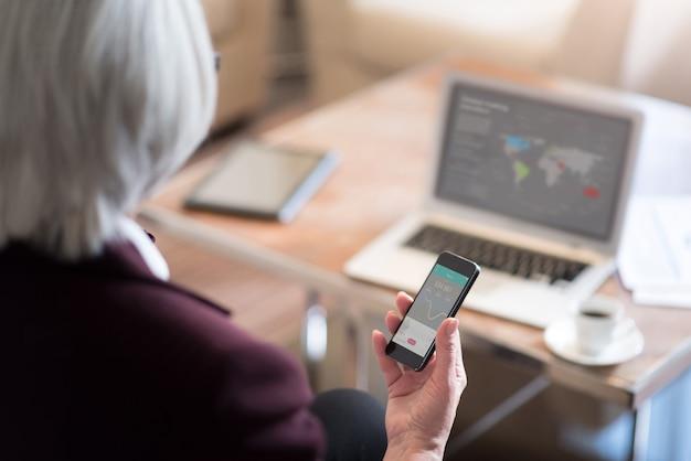 Gadget moderni. piacevole bella donna di affari invecchiata tenendo il telefono mentre è seduto in ufficio davanti al computer portatile e lavorando