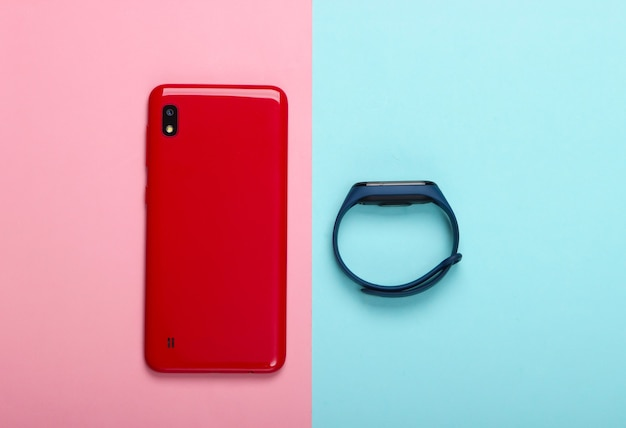 Gadget moderni. smartphone e braccialetto intelligente su blu rosa