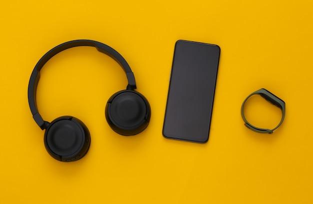Gadget moderni. smartphone con cuffie stereo nere e braccialetto intelligente su sfondo giallo