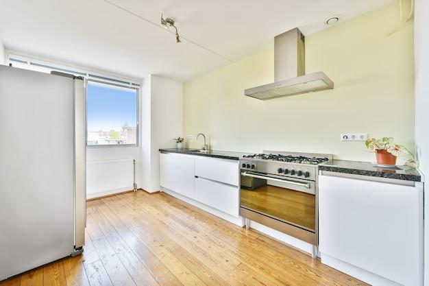 Cucina moderna con armadi in legno e design minimalista in monolocale mansardato con pareti bianche