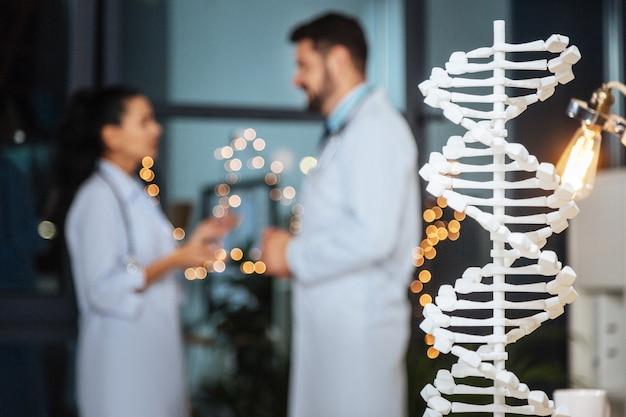 Genetica moderna. messa a fuoco selettiva di un modello di dna con simpatici ricercatori genetici intelligenti che parlano in background