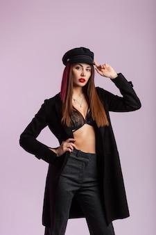 La modella moderna della ragazza raddrizza il berretto nero alla moda all'interno. elegante giovane donna in giacca vintage in biancheria intima di pizzo chic in pantaloni alla moda con labbra rosse sexy in studio vicino al muro.