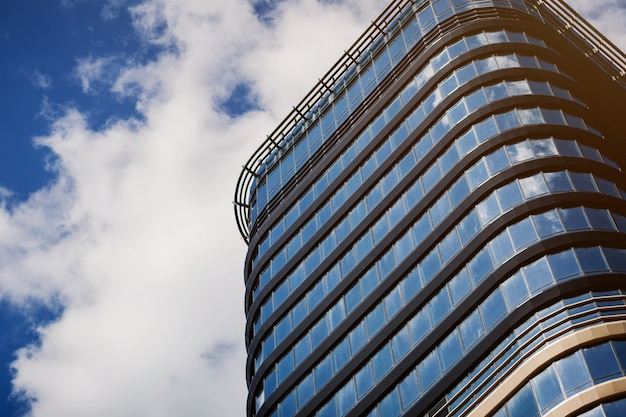 Grattacieli moderni della costruzione di vetro del centro commerciale sul fondo del cielo