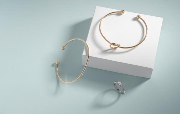 Braccialetti d'oro moderni e anello di diamanti su sfondo bianco e blu con spazio di copia