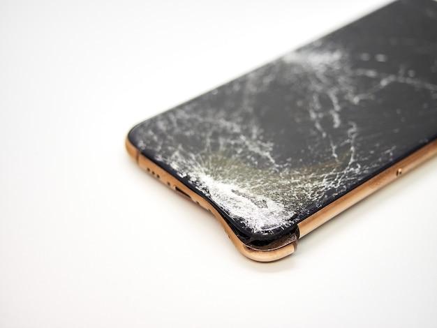 Un moderno smartphone color oro con un display in vetro rotto e un primo piano del corpo curvo danneggiato isolato su superficie bianca