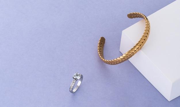 Bracciale d'oro moderno e anello di diamanti su sfondo di carta bianca e blu con spazio di copia