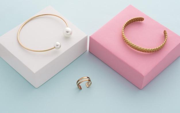Braccialetti d'oro moderni su scatole rosa e bianche e anello a doppia forma su sfondo blu