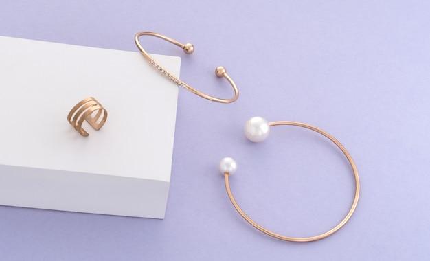 Braccialetti e anello dorati moderni sulla scatola bianca su fondo porpora con lo spazio della copia