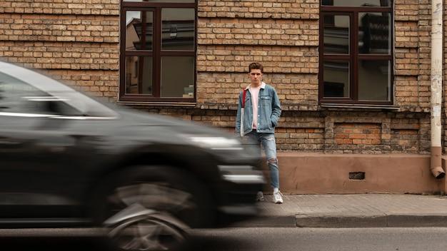 Un giovane di bell'aspetto moderno in giacca di jeans blu alla moda si trova sulla strada vicino alla strada oltre le auto in movimento. il ragazzo alla moda in vestiti casuali dei jeans della gioventù alla moda sta camminando all'aperto. traffico cittadino.