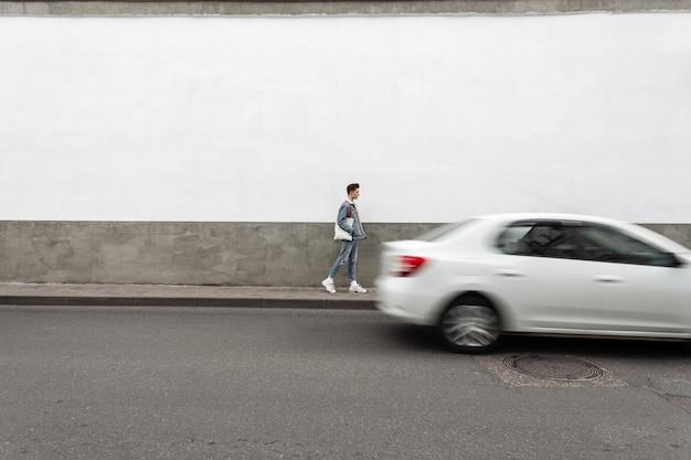 Giovane moderno di bell'aspetto in vestiti alla moda blue jeans in scarpe bianche con borsa in tessuto viaggio su strada vicino alla strada con trasporto in movimento. il ragazzo urbano alla moda si diverte a camminare vicino al muro grigio