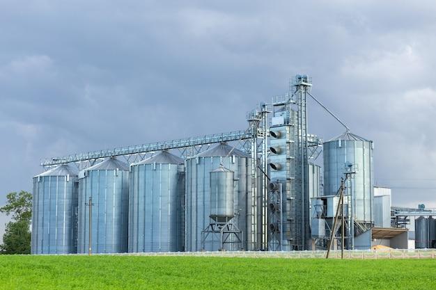 Moderno elevatore per granaio e linea di pulizia dei semi. silos d'argento su impianti di lavorazione e produzione agroalimentari per lo stoccaggio e la lavorazione dell'essiccamento di prodotti agricoli, farine, cereali e grano.