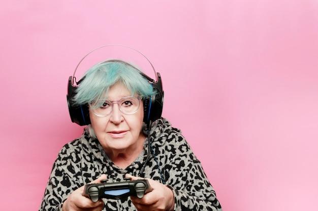 La nonna moderna con i capelli blu che gioca a un videogioco con le cuffie e il telecomando ha una fotocamera