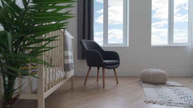 La sedia e lo sgabello grigi moderni sbuffano sulla coperta tessuta in camera da letto infantile