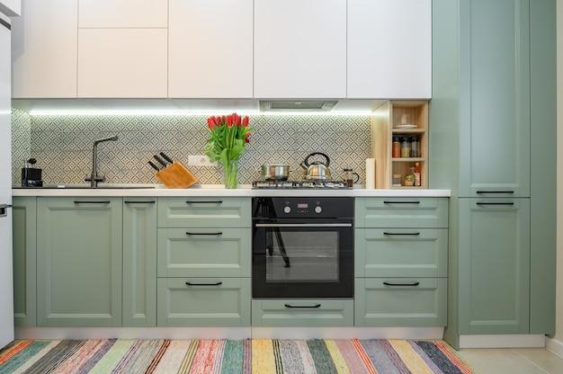 Vista frontale della mobilia interna della cucina moderna greenteal