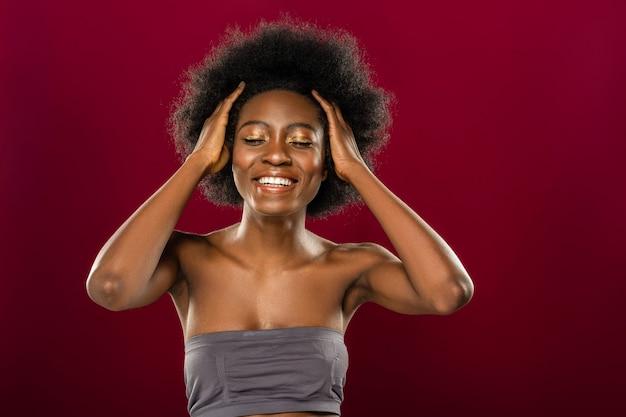 Acconciatura moderna. felice donna positiva chiudendo gli occhi mentre si tocca i capelli