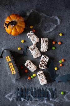 Sfondo moderno di halloween. biscotti di halloween. mostri divertenti fatti di biscotti con cioccolato sul tavolo