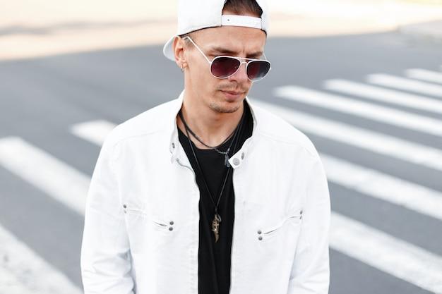 Uomo moderno bello giovane hipster in occhiali rotondi alla moda in una giacca bianca estiva in un berretto da baseball alla moda in una maglietta nera si trova sulla strada in città
