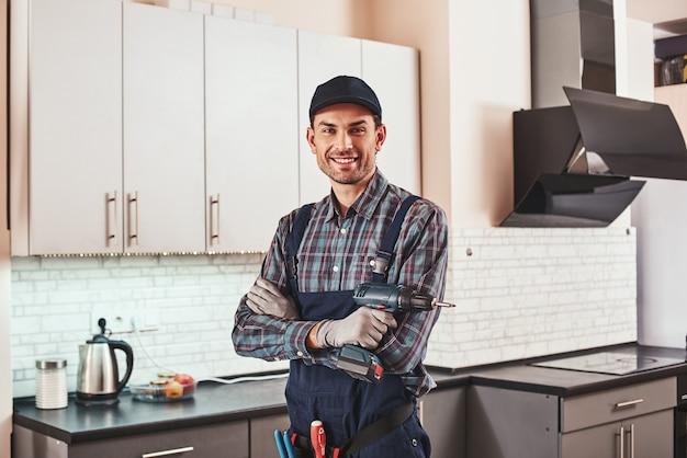 Ritratto moderno tuttofare di un caposquadra maschio sorridente in piedi con perforatore