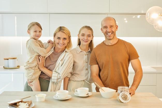 Moderna famiglia felice gustando la colazione insieme in piedi a tavola in cucina interna