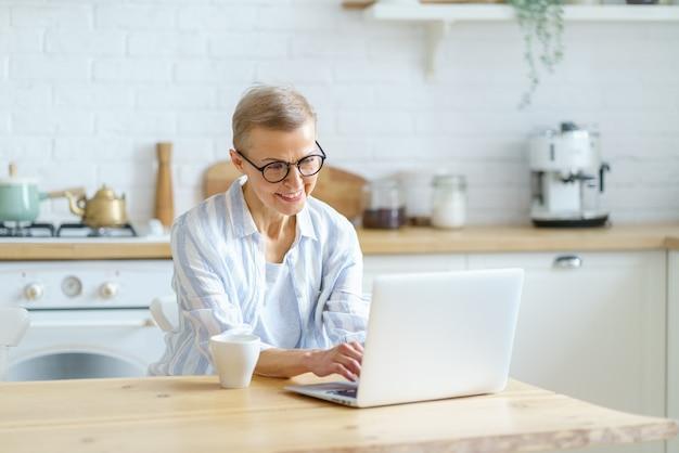 Moderna donna matura felice con gli occhiali che lavora o studia sul laptop mentre è seduta in cucina a