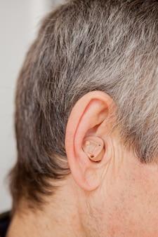 Apparecchio acustico moderno nell'orecchio di un vecchio