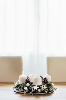 Interni domestici moderni con corona dell'avvento prima candela accesa contando quattro settimane fino a natale