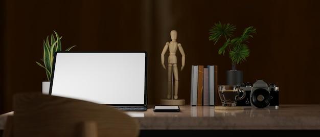 La moderna stanza dell'ufficio domestico nell'oscurità si chiude sul rendering 3d del mockup dello schermo del tablet della scrivania da lavoro