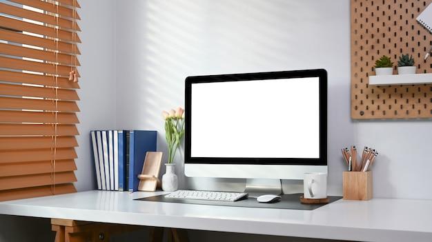 Ministero degli interni moderno con computer, libri e forniture per ufficio sul tavolo bianco.