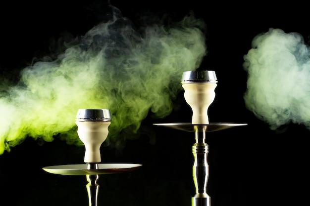 Narghilè moderno con fumo nella luce del club scuro