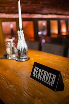 Un'idea moderna per un tavolo riservato con la scritta prenotazione del tuo posto. idea ristoranti l'iscrizione riservata su un tavolo di legno in un caffè.
