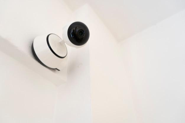 Moderna telecamera di sicurezza domestica o di sorveglianza per interni installata a parete. concetto di sicurezza domestica, sorveglianza remota, sorveglianza.