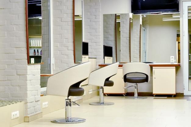 Interiore moderno del salone di bellezza e del posto di lavoro dello specialista di bellezza. spazio di lavoro in un salone di bellezza per un parrucchiere. interno di un parrucchiere nei colori beige bianco chiaro