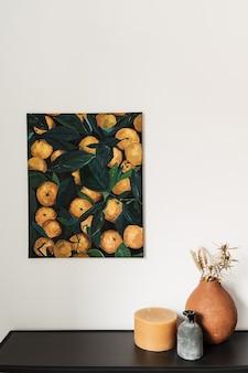Concetto di interior design moderno. tela di pittura a olio con arance sul muro. candela, vaso di terracotta con piante secche.