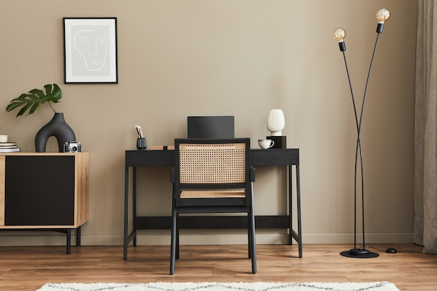 Interior design moderno dello spazio dell'ufficio domestico con sedia elegante, scrivania, comò, cornice nera per poster, laptop, libro, forniture per ufficio ed eleganti accessori personali nell'arredamento della casa