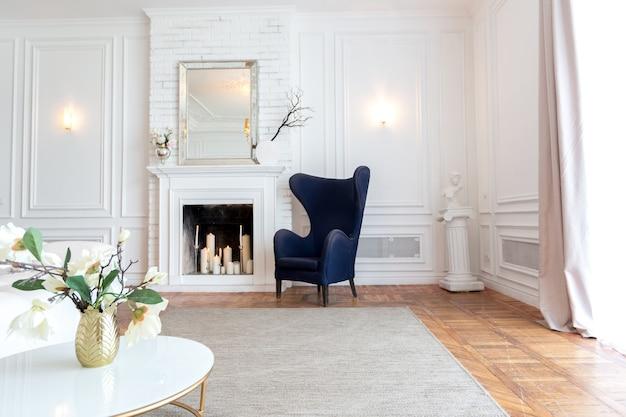 Interni moderni di un lussuoso soggiorno ampio e luminoso. divano bianco costoso e scaffalature in legno, pareti bianche con modanature e un lampadario di lusso