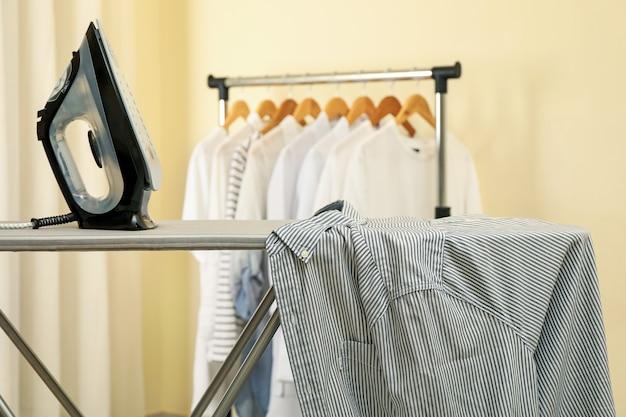 Ferro da stiro moderno sull'asse da stiro con camicia, spazio per il testo