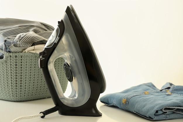 Ferro da stiro moderno e lavanderia sul tavolo bianco