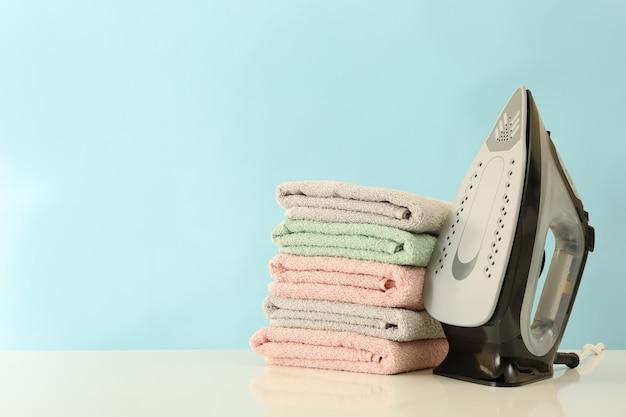 Ferro da stiro moderno e pila di asciugamani sul tavolo bianco