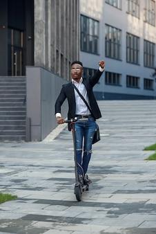 L'uomo d'affari afroamericano moderno e gioioso cavalca uno scooter elettrico dopo aver terminato la sua giornata lavorativa
