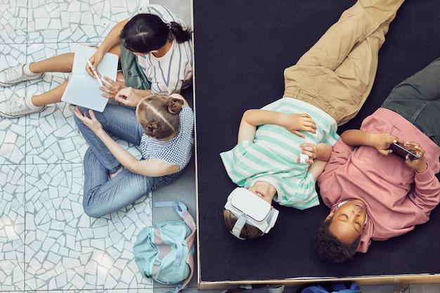 Bambini moderni che si rilassano nella lounge della scuola