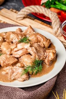 Cucina moderna. carne di suino cotta sottovuoto con tecnologia sous vide. sugo di carne in un piatto bianco