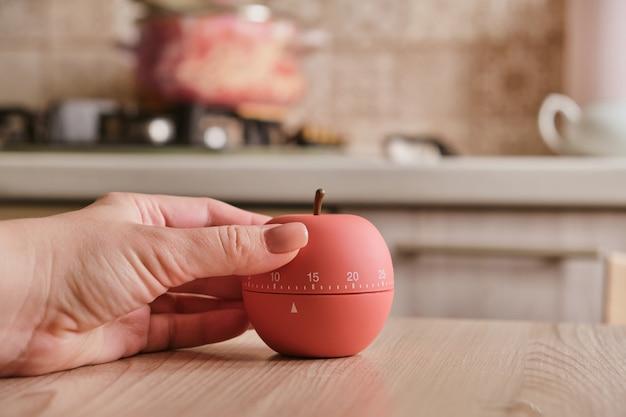 Timer da cucina moderno a forma di mela sullo sfondo della cucina