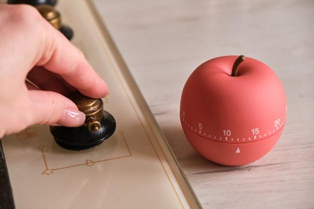 Timer da cucina moderno a forma di mela vicino al piano cottura in cucina